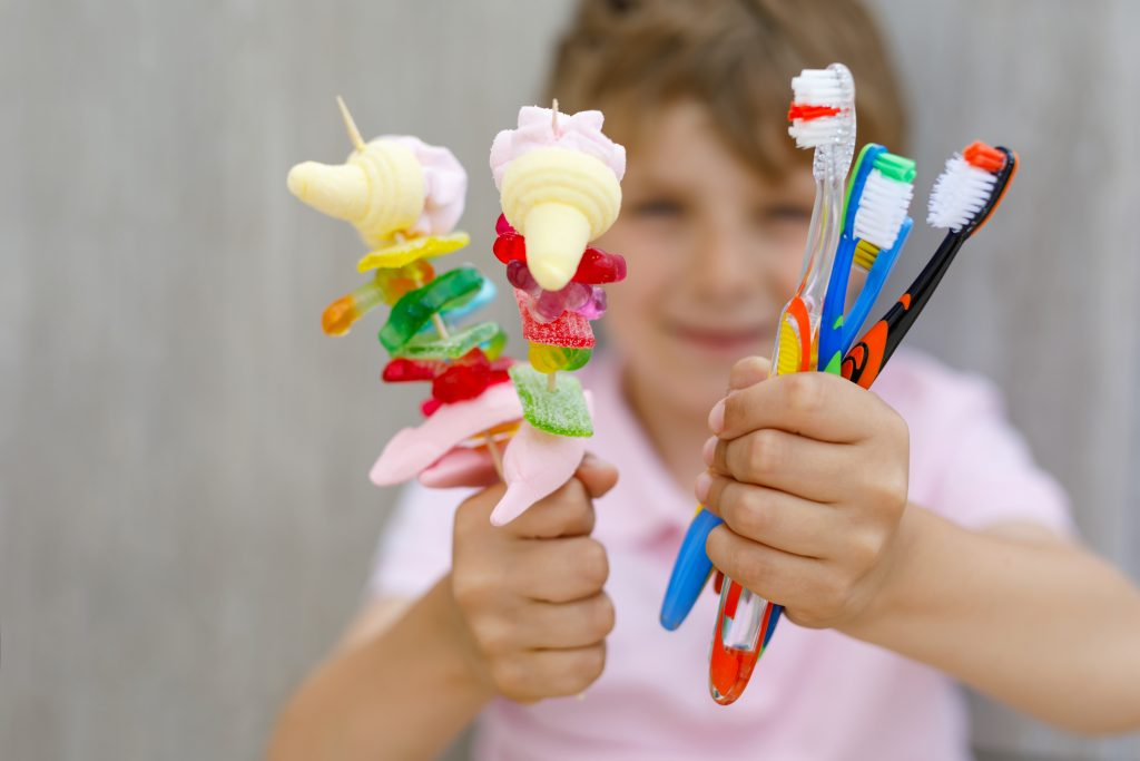 Child With Toothbrushes And Sweets 1024x683
